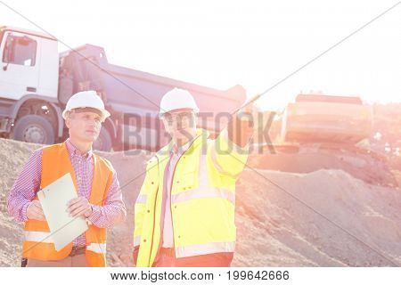 Supervisor showing something to colleague while discussing at construction site