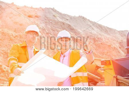 Engineers discussing over blueprint at construction site