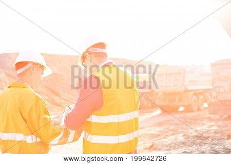Engineers writing on clipboard at construction site against clear sky