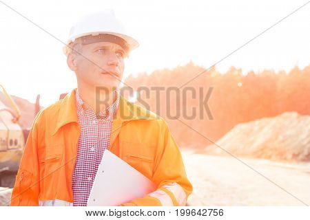 Thoughtful engineer holding clipboard against clear sky