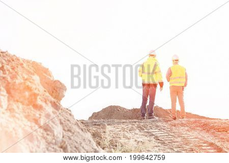 Rear view of supervisors standing at construction site against clear sky