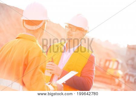 Architects discussing at construction site on sunny day