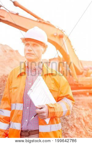 Architect looking away while holding clipboard at construction site