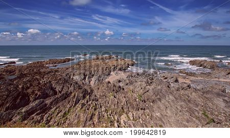 Rocky and dangerous shore next to the beach of Voulakombe. Sunny day. Low tide. Devon. England