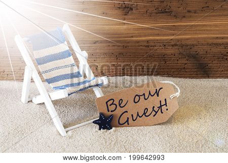 Sunny Summer Label With Sand And Aged Wooden Background. English Text Be Our Guest. Deck Chair For Holiday Or Vacation Feeling.