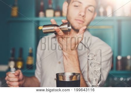 Professional bartender in bar interior pouring syrup into measuring glass for making cocktail. Service industry occupation.