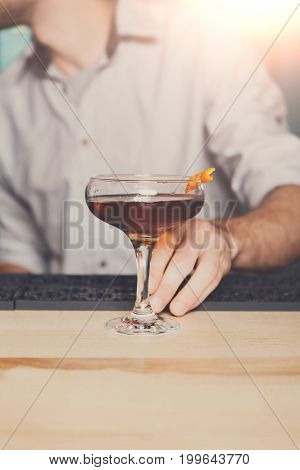 Unrecognizable bartender offers alcoholic cocktail in night club bar. Focused on glass