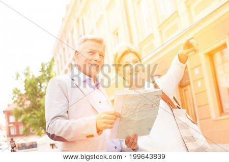 Middle-aged woman showing something to man with road map in city