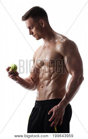 Athletic shirtless young male fitness model posing with green apple on white background