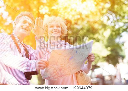 Happy middle-aged couple holding map in city
