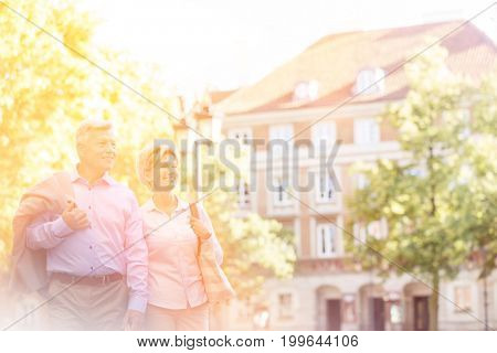 Happy middle-aged couple walking in city