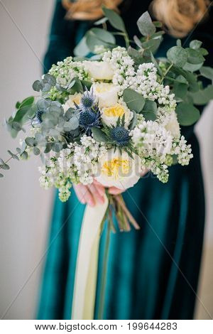 beautiful decorate wedding bouqet in bride hands in green dress