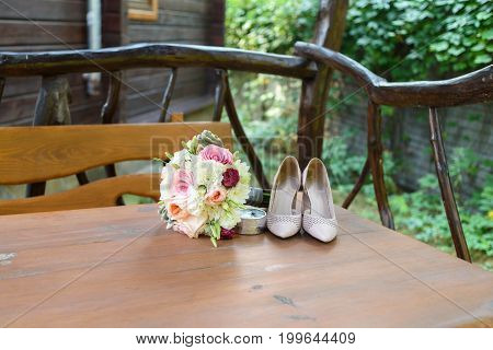 Fresh Wedding Bouquet, Box With Rings And  Beige Shoes Stand On Wooden Table Outdoor, Free Space.  W