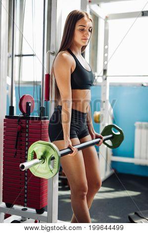 Sportswoman Lifting Hard Barbell At Gym Interior