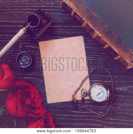 Beautiful vintage background (sheet of paper three red roses dip pen with an ink-pot ancient book and an antique pocket watch with a heart-shaped chain on a worn black wooden background) specially toned in a retro style