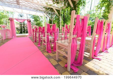 Empty Wedding Chairs On Each Side Of Archway. Place For Wedding Ceremony Decorated In Pink Color,  W