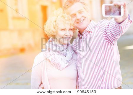 Happy middle-aged couple taking selfie through smart phone in city