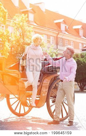 Full-length of middle-aged man assisting woman out of horse cart