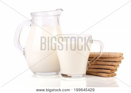 jug and glass of milk with stack of grain crispbreads isolated on white background.