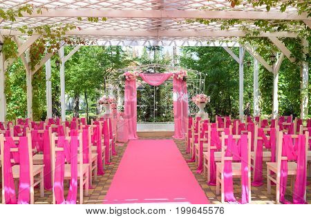 Place For Wedding Ceremony In Pink Color With Wedding Arch Decorated With Flowers And Pink Cloth And