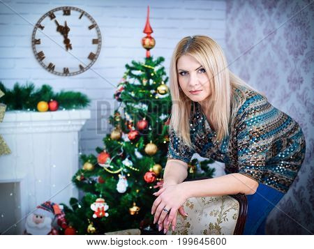 Portrait of smiling young woman showing clock in front of christmas tree