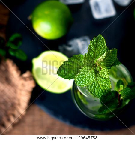 Fresh mojito drink coctail with lime and mint in a glass on black stone board and wooden rustic table