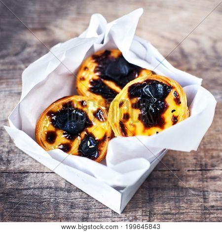 Fresh Pasteis de Nata - creamy egg tart with sweet curstard black crust and sugar powder on wooden background. Pasteis de Belem pastry