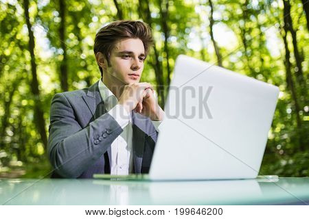 Portrait Of Thinking Businessman Sitting At The Office Desk Work At Laptop Computer In Green Forest
