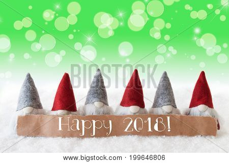 Label With English Text Happy 2018 For Happy New Year. Christmas Greeting Card With Gnomes. Sparkling Bokeh And Green Background With Snow And Stars.