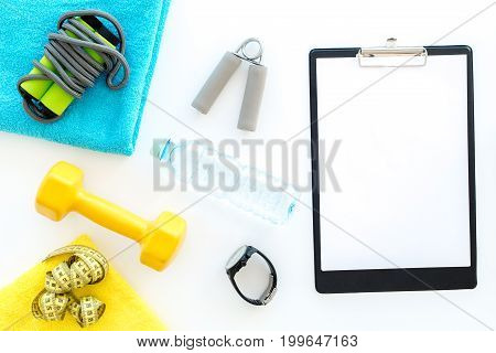 Equipment for fitness. Jump rope and expander on white background top view.
