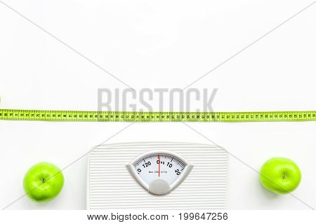 Bathroom scale and apples on white background top view.