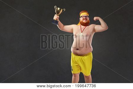 A fat naked man with a champion's cup in his hands. Humor sports concept.