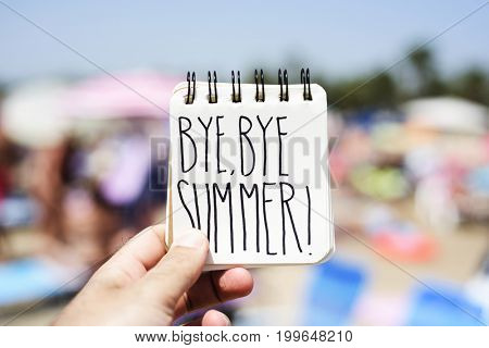 closeup of a young man in the beach showing a spiral notepad with the text bye bye summer handwritten in it