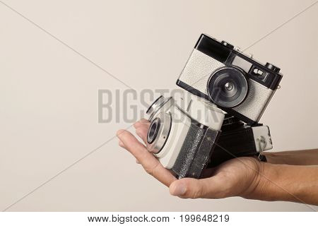 closeup of a young man with a pile of old film cameras in his hands, against an off-white background with a blank space on the left