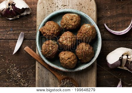 high-angle shot of some falafel served in a green earthenware plate placed on a rustic wooden table