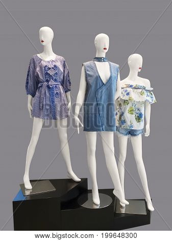 Three female mannequins dressed in fashionable clothes isolated on white background. No brand names or copyright objects.
