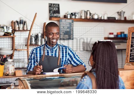 Smiling young African barista standing at the counter of a cafe talking to a customer and writing down an order in a notebook