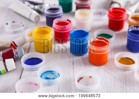 Artist workplace. Set of color gouache jars and acrylic paints on white wooden desk background, copy space