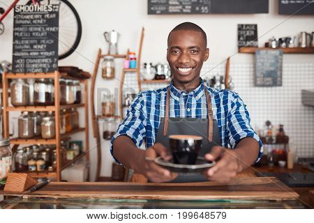 Portrait of a friendly young African barista standing at the counter of a trendy cafe holding a fresh cup of cappuccino