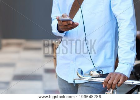 Closeup of a stylishly dressed young African man texting on his cellphone while standing with his bicycle on a city street