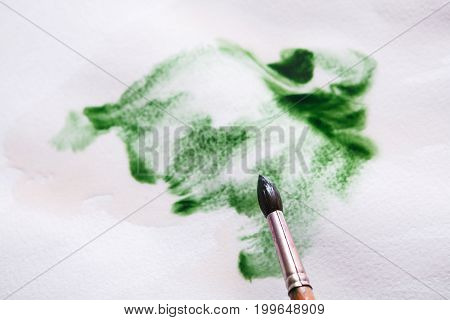 Artist creating watercolor painting. Expressive brush strokes of green aquarelle on paper texture. Modern art backgroung with copy space