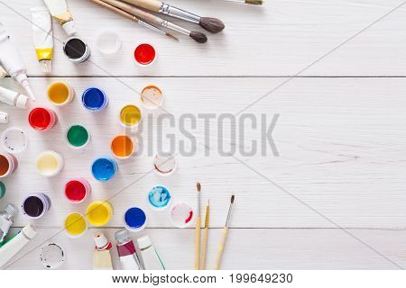 Artist workplace. Set of color gouache jars and acrylic paints on white wooden desk background, top view, copy space