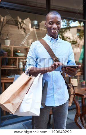 Portrait of a stylish young African man smiling and using a digital tablet while standing with shopping bags on a city street