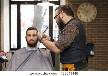Barber make haircut with trimmer hair clipper in barbershop. Hairstyle in male hair salon