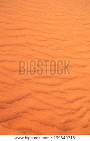 Texture of sand dune of orange color in desert, UAE