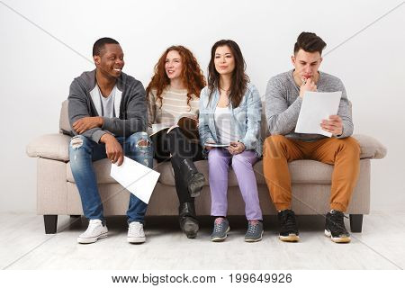 Multiethnic young students studying, preparing for exam, sitting on sofa in living room, studio shot