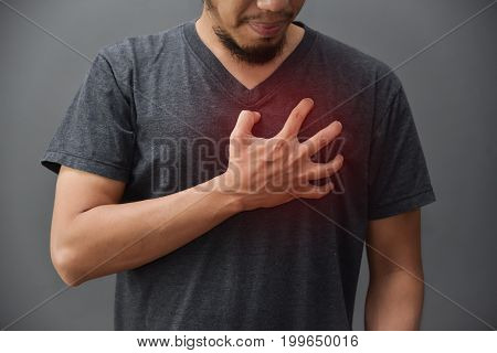 Asian beard man in gray shirt having chest pain from heart attack on grey background. Illness exhausted disease tired for overtime working concept.