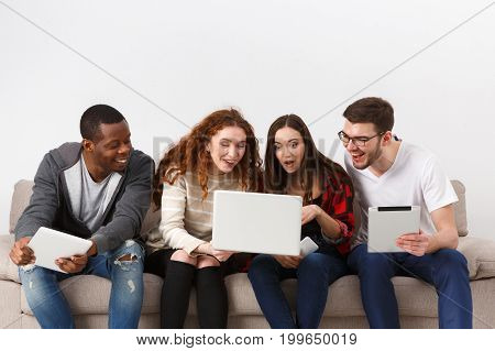 Friends watch movie on laptop. Young happy people in casual clothes using gadget while sitting indoors