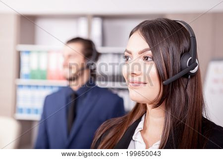 Woman working at the customer support and her colleague blurred in background. Help desk and support