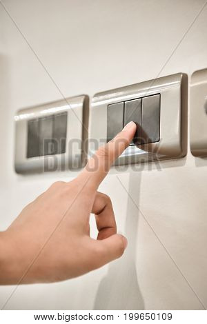 Close up hand turning on or off on grey light switches. Copy space.